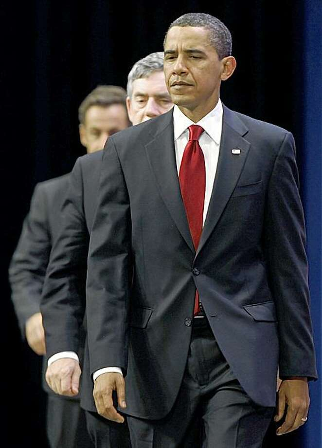 President Barack Obama, followed by British Prime Minister Gordon Brown, center, and French President Nicolas Sarkozy arrives to make a statement on Iran's nuclear facility, Friday, Sept. 25, 2009, during the G-20 Summit in Pittsburgh. (AP Photo/Gerald Herbert) Photo: Gerald Herbert, AP