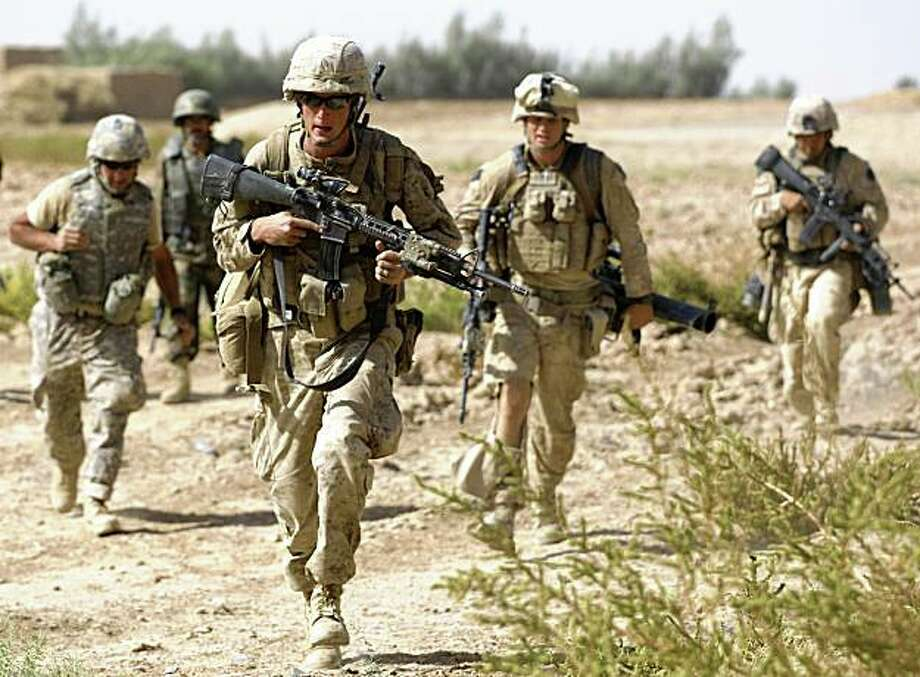 During a firefight with Taliban militants, U.S. Marine Cpl. Matthew Doherty, of Bastrop, Texas, center left, runs for a new position with a group of fellow Marines with 3rd Platoon, Bravo Company, 1st Battalion 5th Marines, and an Afghan soldier, and an interpreter, left, in Nawa district, Helmand province, southern Afghanistan, Sunday, Oct. 4, 2009. (AP Photo/Brennan Linsley) Photo: Brennan Linsley, AP