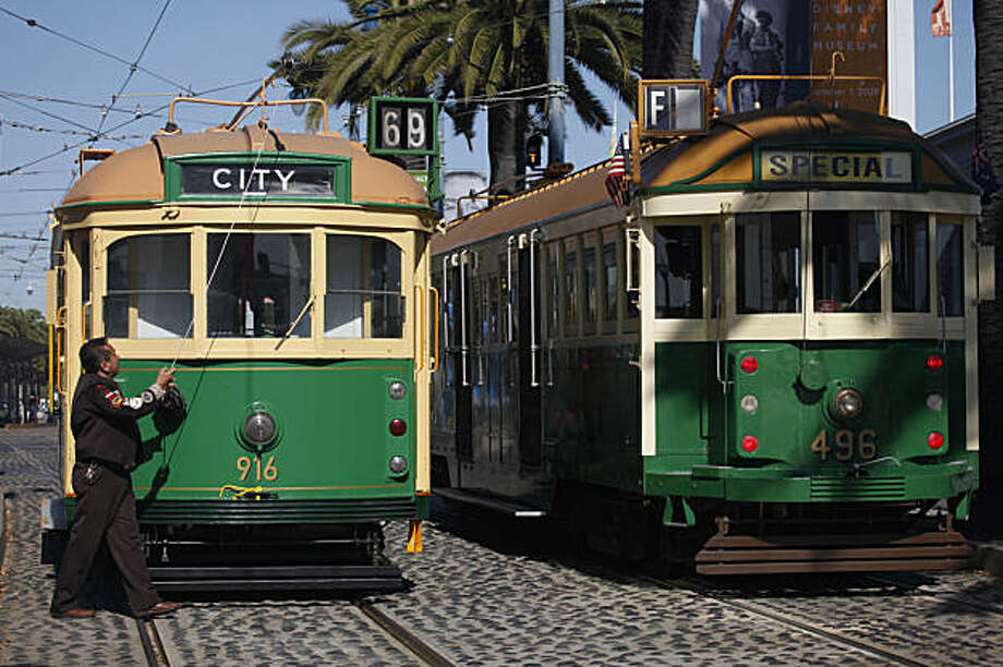 Nelson Alfaro works in front of the new Melbourne Tram No. 916 (left) that will join San Francisco's historic streetcar line. Photo: Lea Suzuki, The Chronicle