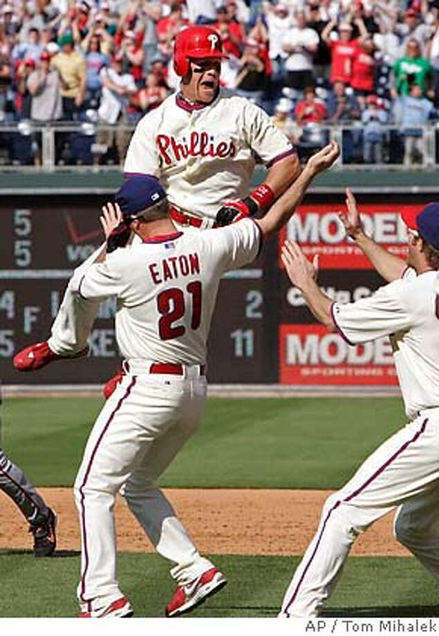 Philadelphia Phillies' Geoff Jenkins, rear, jumps in the air near Adam Eaton, left, and Jason Werth, right, after the Phillies defeated the San Francisco Giants' 6-5 in a baseball game, Sunday, May 4, 2008 in Philadelphia. (AP Photo/Tom Mihalek) Photo: Tom Mihalek