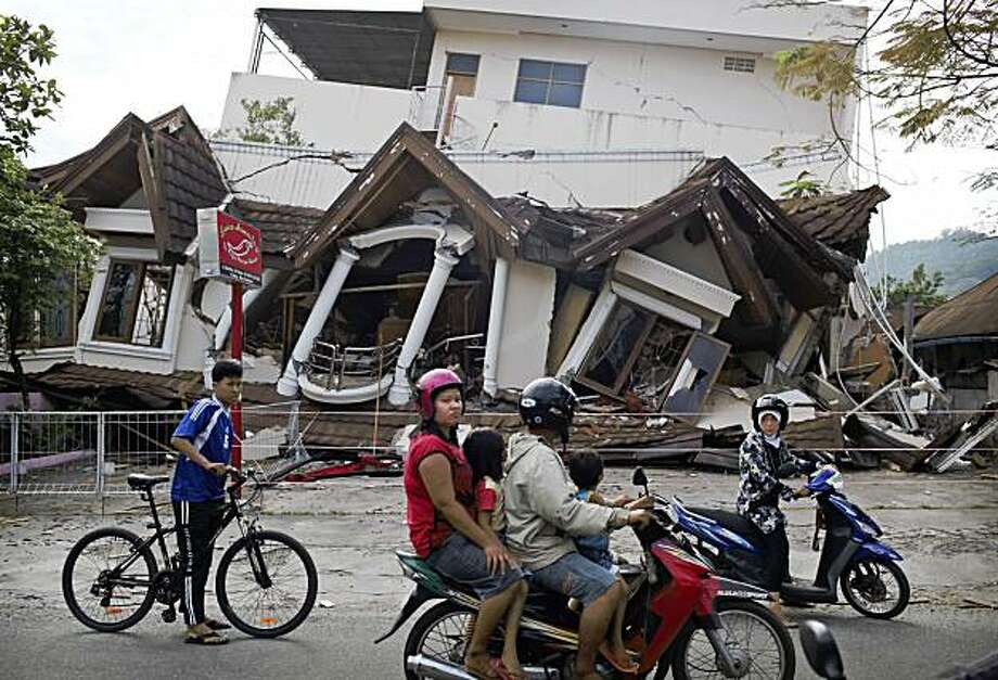 Indonesians pass a collapsed building Saturday, Oct. 3, 2009 in the Sumatran Island city of Padang, Indonesia, three days after Wednesday's 7.6-magnitude quake that toppled thousands of buildings. (AP Photo/Kevin Frayer) Photo: Kevin Frayer, AP