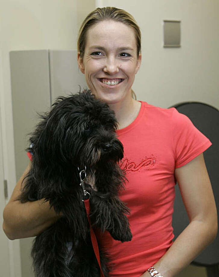 Belgium's Justine Henin poses with her dog, after a press conference, in Limelette, Belgium, Wednesday Sept. 23, 2009. Former No. 1 Justine Henin has announced her return to competitive tennis for next year. Henin had been retired for just over a year, but at 27 she says has the fire and physical strength to compete for an eighth Grand Slam title. (AP Photo/Yves Logghe) Photo: Yves Logghe, AP