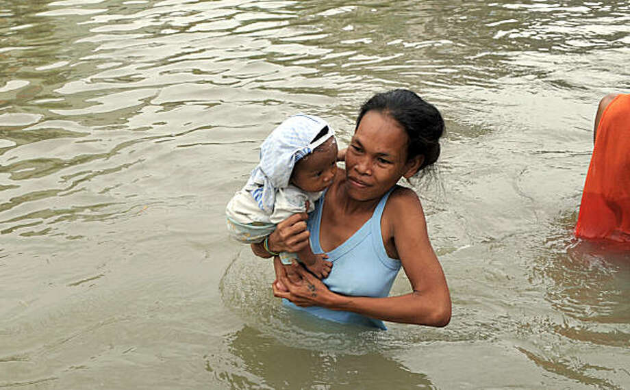 "A woman carrying her child wades through a flooded street as they go along with their daily business in the town of Taytay, Rizal province east of of Manila on October 2, 2009. President Gloria Arroyo on October 2 placed the entire Philippines under a ""state of calamity,"" as a powerful typhoon threatened more devastation following deadly floods, her spokesman said.    AFP PHOTO/TED ALJIBE (Photo credit should read TED ALJIBE/AFP/Getty Images) Photo: Ted Aljibe, AFP/Getty Images"