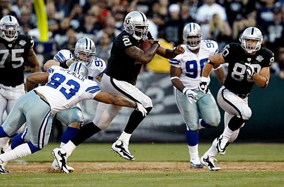 Raiders JaMarcus Russell takes off for a first down in first quarter action . The Oakland Raiders lead the Dallas Cowboys in their first pre-season game in Oakland 17-7 in 3rd quarter Thursday Aug 13, 2009. Photo: Lance Iversen, The Chronicle