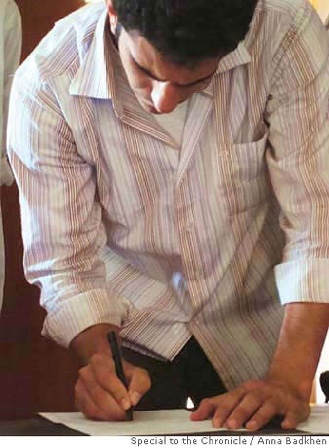 Mohammed al-Rubaye signs a document saying he will not participate in violence against Iraqis or Americans. Al-Rubaye, a Shiite, had spent nine months in jail after being convicted of attacking U.S. and Iraqi troops and Sunni civilians. Ran on: 05-08-2008  Mohammed al-Rubaye signs a document saying he will not participate in violence against Iraqis or Americans. Photo: By Anna Badkhen