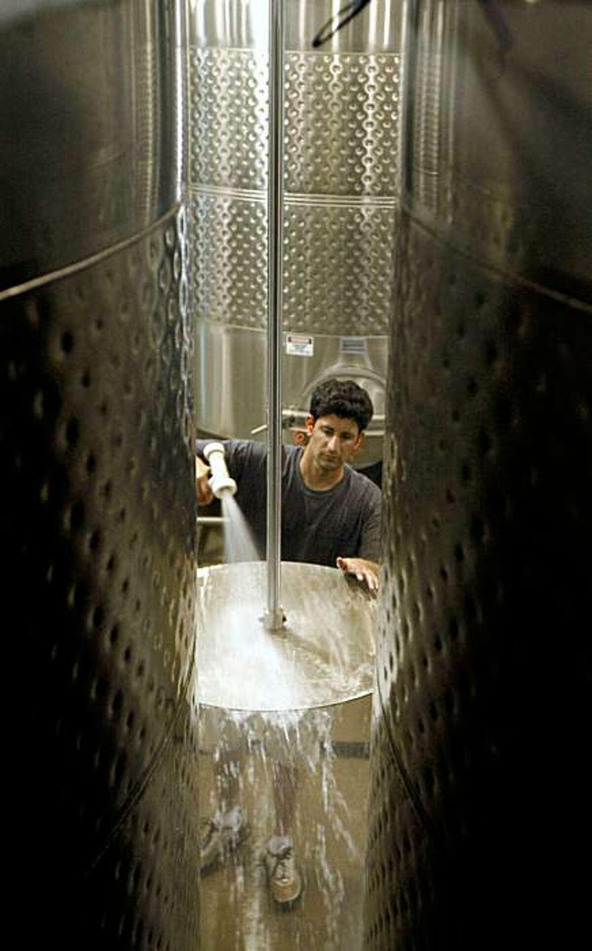 Daniel Seddiqui cleans a powered paddle used to punch down the grapes in large holding tanks before the wine is transferred to French oak barrels Tuesday Sept 22, 2009. Seddiqui found himself unemployed after graduating from USC with little chance of finding a job in the down ecomamy he elected to visit 50 Sates and experience 50 different jobs in as many weeks. He concluded his travels working at Domaine Carneros in Napa helping bring in the wine harvest. Sept 22, 2009
