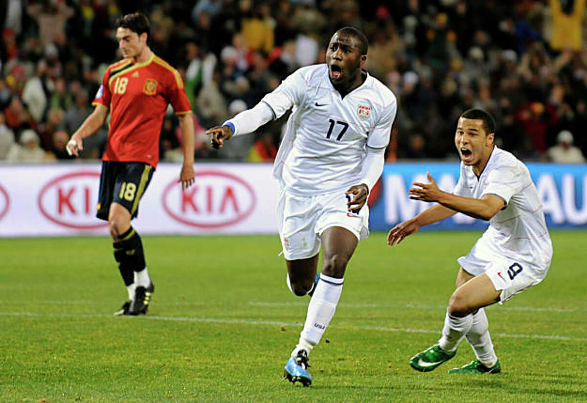 USA's Jozy Altidore, center, reacts after scoring a goal, with fellow team member USA's Charlie Davies, right, as Spain's Albert Riera, left, looks on, during their Confederations Cup semifinal soccer match at Free State Stadium in Bloemfontein, South Africa, Wednesday, June 24, 2009. (AP Photo/Martin Meissner)