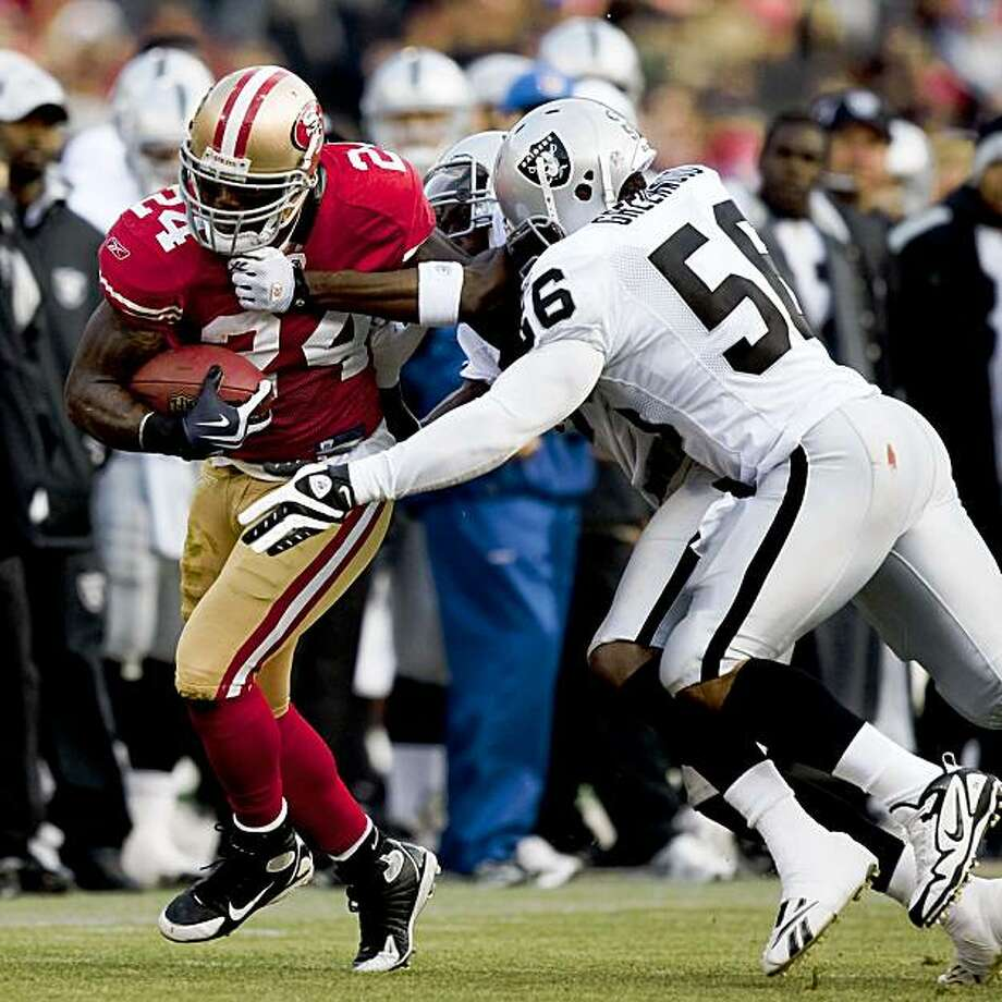 Running back Michael Robinson (24) of the San Francisco 49ers runs the ball as he is tackled by linebacker Slade Morris (58) of the Oakland Raiders during a preseason game at Candlestick Park in San Francisco, Calif. on Saturday, Aug. 22, 2009. Photo: Stephen Lam, The Chronicle