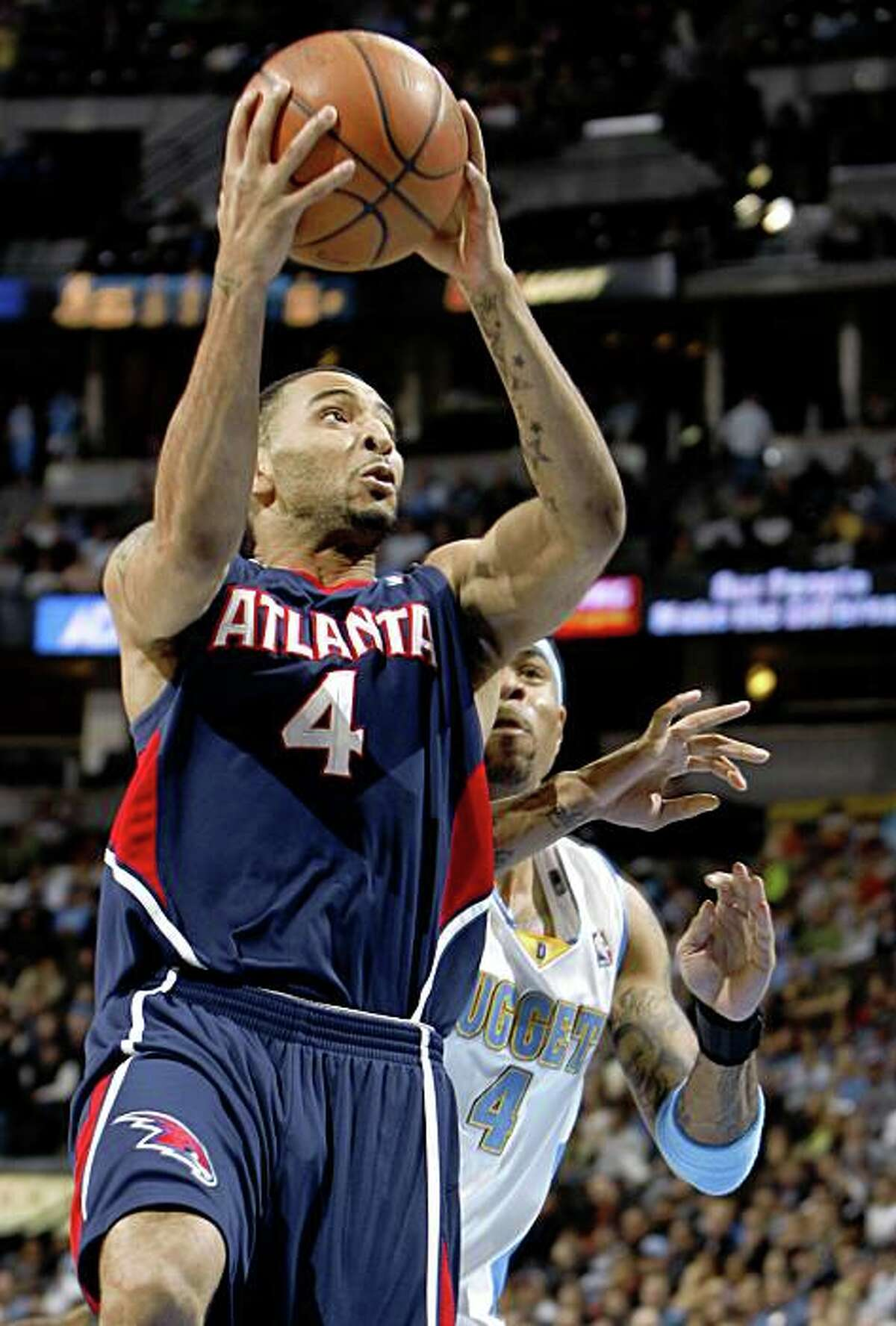 FILE - In this Feb. 25, 2009, file photo, Atlanta Hawks guard Acie Law, left, slips past Denver Nuggets forward Kenyon Martin for a basket during the first quarter of an NBA basketball game in Denver. A person with knowledge of the negotiations says the Hawks and Golden State Warriors are working on a trade that would send point guard Jamal Crawford to Atlanta for guards Acie Law and Speedy Claxton. Crawford can't be traded until July 1 or until he signs paperwork indicating he won't opt out of his contract and become a free agent. (AP Photo/David Zalubowski, File)
