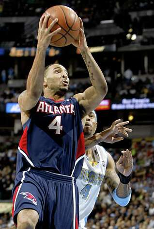 FILE - In this Feb. 25, 2009, file photo, Atlanta Hawks guard Acie Law, left, slips past Denver Nuggets forward Kenyon Martin for a basket during the first quarter of an NBA basketball game in Denver. A person with knowledge of the negotiations says the  Hawks and Golden State Warriors are working on a trade that would send point guard Jamal Crawford to Atlanta for guards Acie Law and Speedy Claxton.  Crawford can't be traded until July 1 or until he signs paperwork indicating he won't opt out of his contract and become a free agent.  (AP Photo/David Zalubowski, File) Photo: David Zalubowski, AP