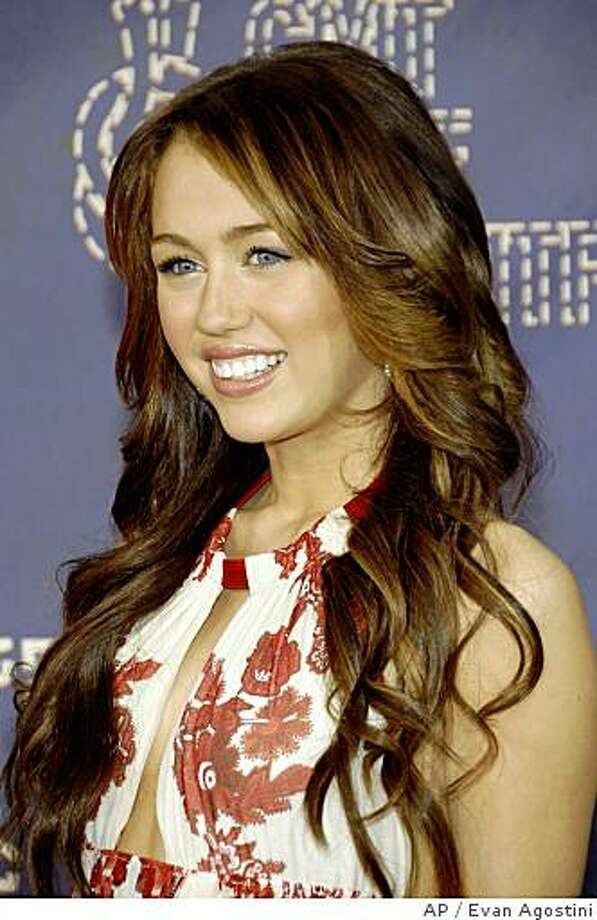 ** CORRECTS BYLINE TO AGOSTINI ** CMT Music Awards show co-host Miley Cyrus arrives at the CMT Music Awards, Monday, April 14, 2008, in Nashville, Tenn. She is co-hosting with her dad, Billy Ray Cyrus.  (AP Photo/Evan Agostini) Photo: Evan Agostini, AP