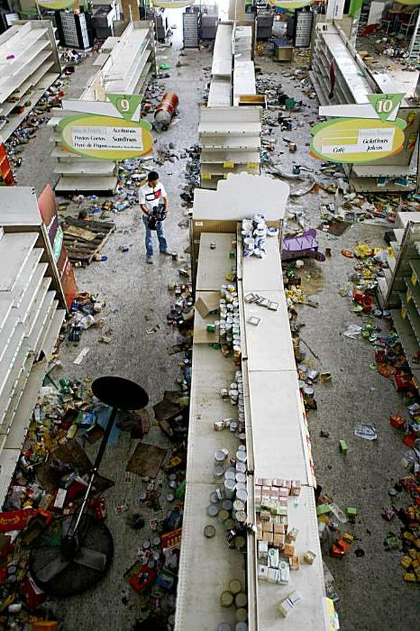 A cameraman takes pictures inside a looted supermarket in El Pedregal neighborhood in Tegucigalpa one day after clashes between supporters of ousted President Manuel Zelaya and police , Wednesday, Sept 23, 2009.  Zelaya spent a second night holed up in the Brazilian embassy  as police fought running battles with his supporters and world leaders called for a peaceful solution to the standoff. Photo: Rodrigo Abd, AP