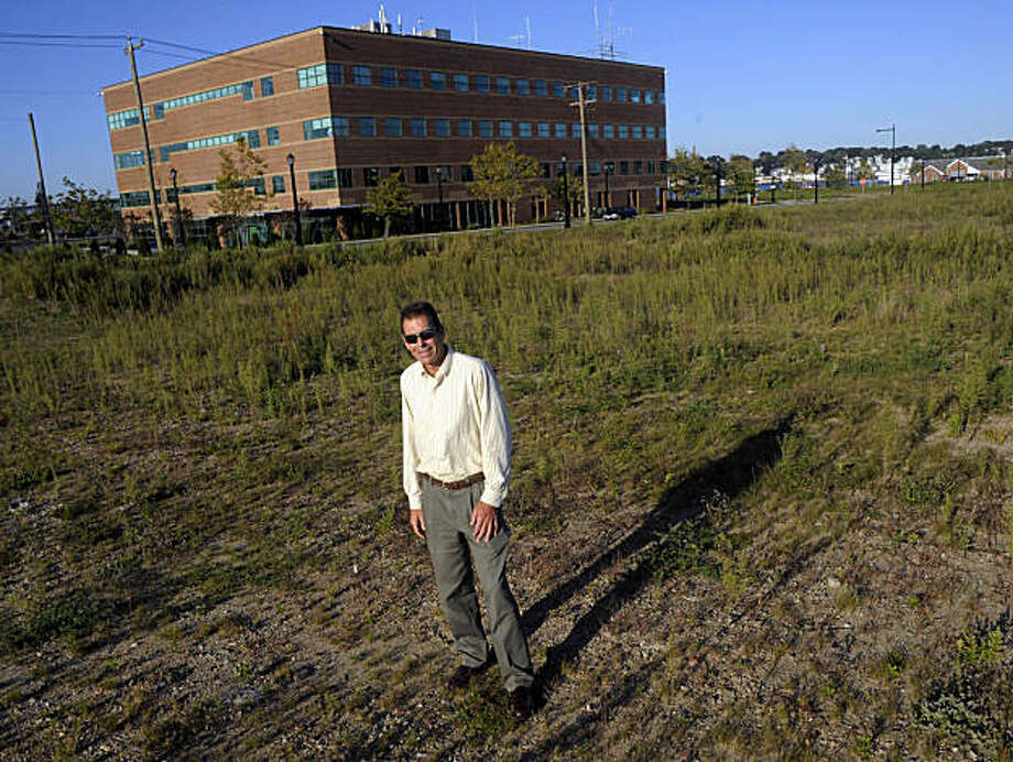 John Brooks, executive director of the New London Development Corp.  stands in a vacant lot in New London, Conn., on Monday, Sept. 21, 2009. The lot, along with 90 nearby acres sits at the heart of an ongoing controversy about the rights of cities to use eminent domain to take property from one private owner for private  development. (AP Photo/Fred Beckham) Photo: Fred Beckham, AP