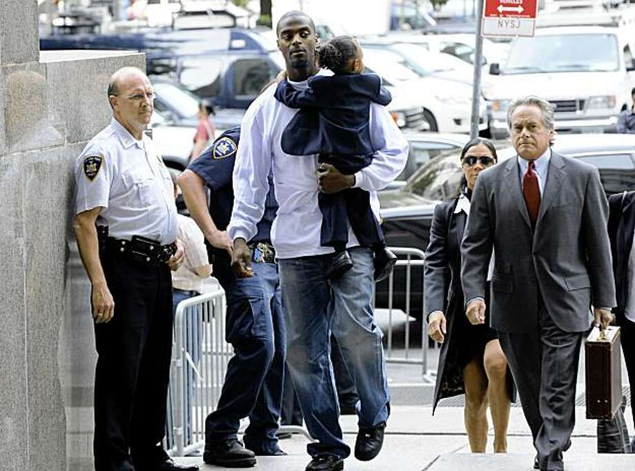 ** THIS CORRECTS THAT BURRESS WAS SENTENCED NOT FOR POSSESSING A GUN, BUT ON A CHARGE OF ATTEMPTED CRIMINAL POSSESSION  OF A WEAPON ** Former Super Bowl star Plaxico Burress carries his son, Elijah, as he arrives at Manhattan criminal  court for his sentencing, Tuesday, Sept. 22, 2009, in New York.  At right is his lawyer, Benjamin Brafman. Burress has been sentenced to two years in prison for attempted criminal possession of a weapon. (AP Photo/ Louis Lanzano) Photo: Louis Lanzano, AP
