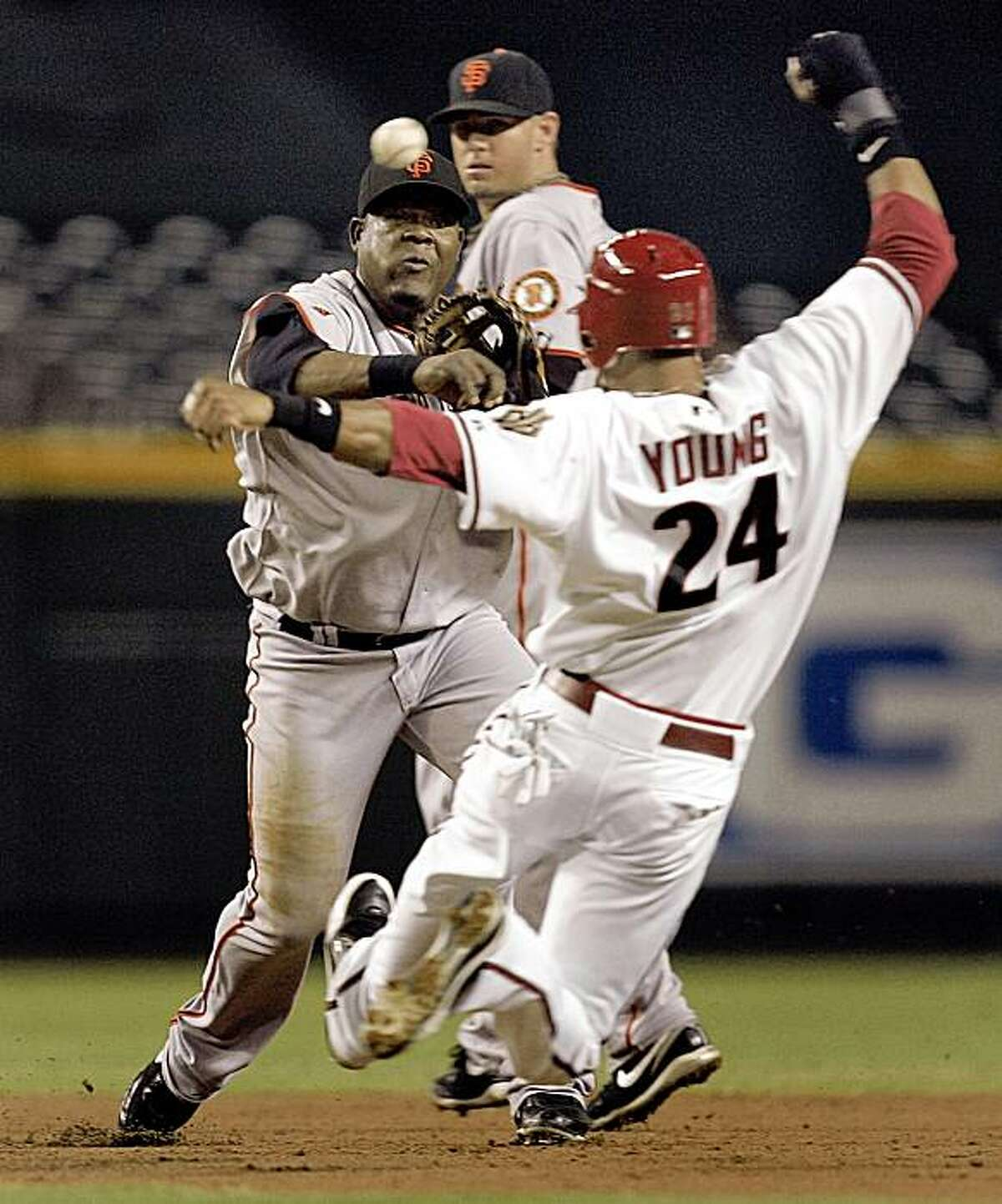 San Francisco Giants' Juan Uribe, left, forces out Arizona Diamondbacks' Chris Young (24) as he turns a double play on Diamondbacks' Stephen Drew during the third inning of a baseball game Monday, Sept. 21, 2009, in Phoenix.