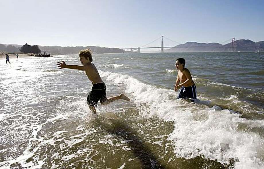 Trent Portman (left) and Miles Yakura play in the surf during a hot day at Crissy Field in San Francisco, Calif., on Friday, September 18, 2009. Photo: Laura Morton, Special To The Chronicle