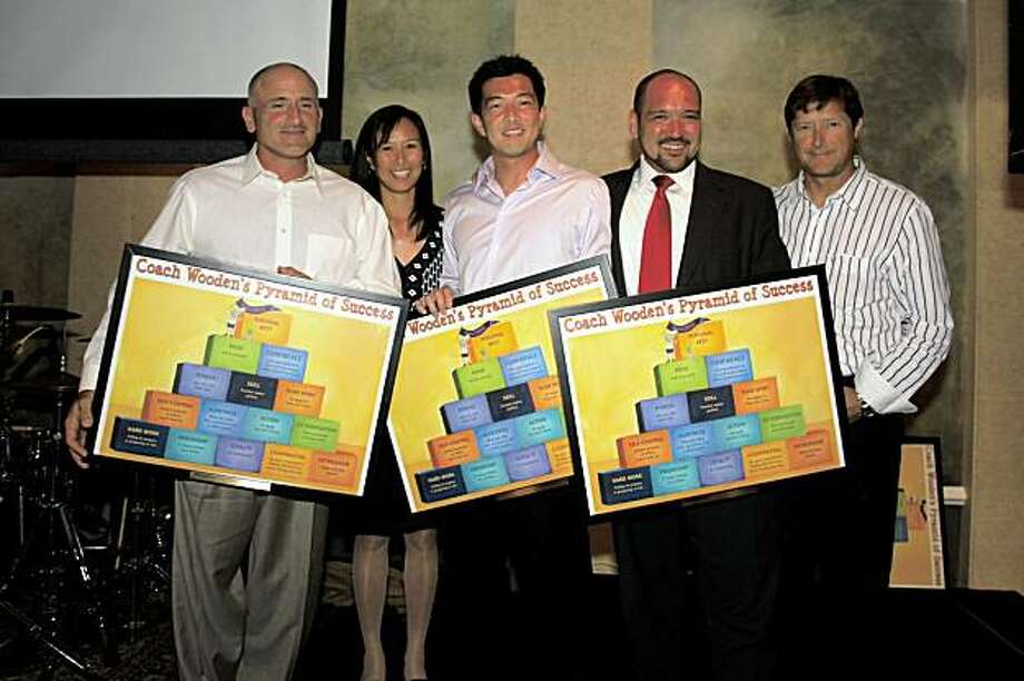 "Harper for Kids co-founders Peanut Louie Harper (2nd from left) and Tim Harper (far right) with Wimbledon sponsors of the Rally for the Kids event (left to right) John Saviano, Julian Cheng and Daniel Brandt. The ""Pyramid of Success"" posters depict character development blocks from.the best-selling children's book by legendary UCLA coach John Wooden, Inch and Miles: The Journey to Success. The Pacific Athletic Club in Redwood City hosted the August 14th Rally for the Kids event to benefit the San Francisco-based nonprofit Harper for Kids. Photo: Rodney Lee, Special To The Chronicle"