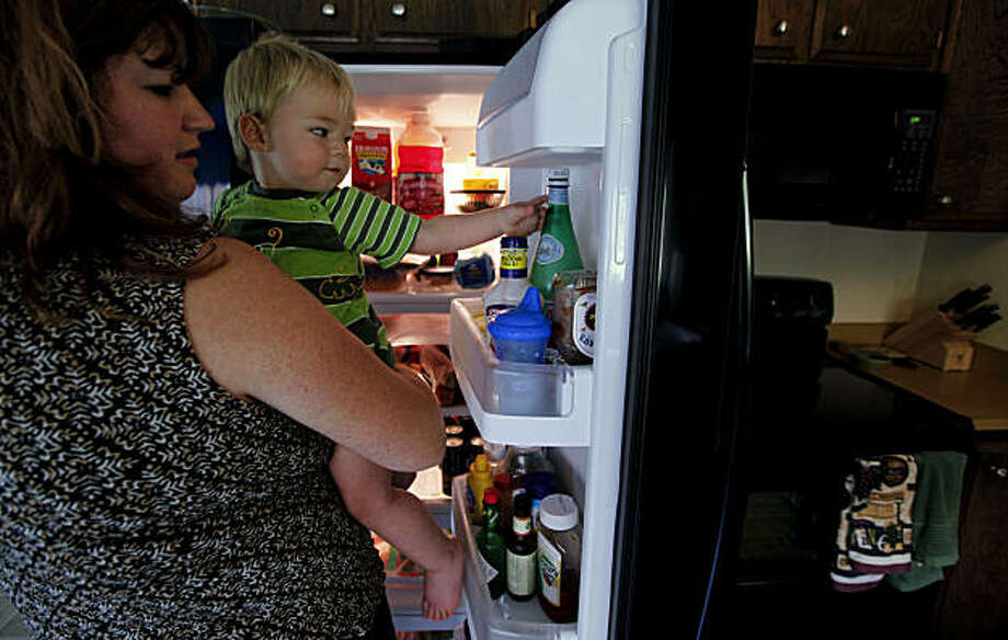 First-time home buyers Jared and Nicole Kitchen of Martinez, Calif., took advantage of the $8,000 federal tax rebate and were able to buy new appliances for their kitchen as well as fill their living room with new furniture. Nicole with the newly purchased refrigerator holds her son, 17-month-old Dillion on Saturday September 26, 2009. Photo: Michael Macor, The Chronicle