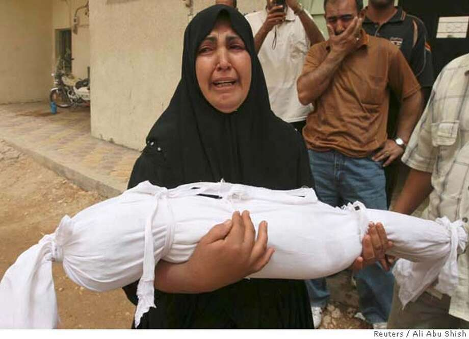 A woman cries while carrying the body of her son wrapped in white cloth for a funeral in Najaf Photo: ALI ABU SHISH