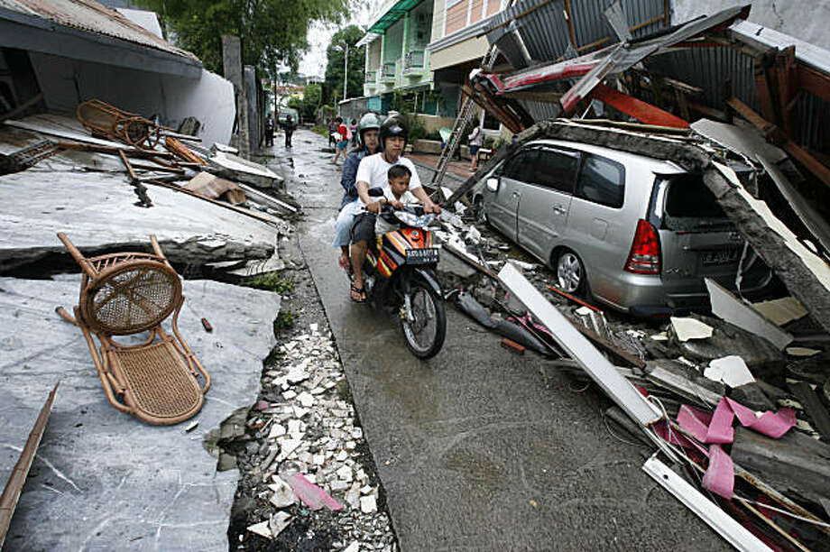 ** CORRECT COUNTRY CODE IN HEADER FIELD ** Residents ride a motorcycle at a neighborhood damaged by earthquake in Padang, West Sumatra, Indonesia, Thursday, Oct. 1, 2009. A second earthquake with a 6.8 magnitude rocked western Indonesia Thursday, a day after the region was devastated by an undersea quake of 7.6 magnitude. (AP Photo/Dita Alangkara) Photo: Dita Alangkara, Associated Press