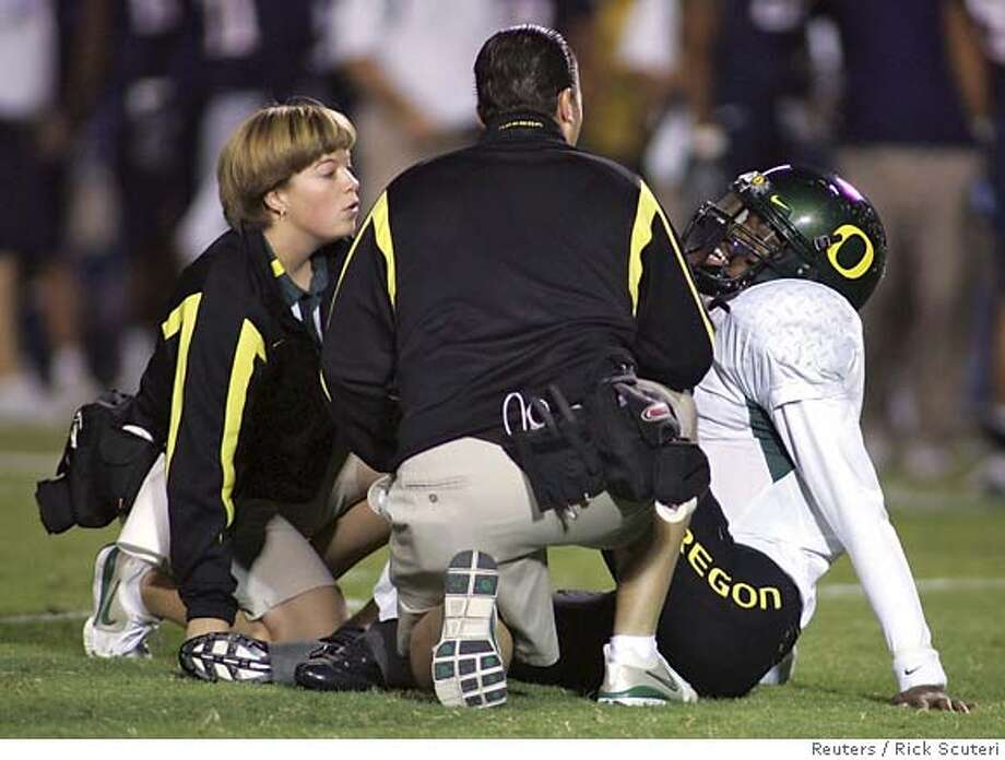 ###Live Caption:Oregon Ducks quarterback Dennis Dixon (R) gets treatment from his trainers during the first quarter of their NCAA football game against the Arizona Wildcats in Tucson, Arizona, November 15, 2007. Dixon left the game. REUTERS/Rick Scuteri (United States)###Caption History:Oregon Ducks quarterback Dennis Dixon (R) gets treatment from his trainers during the first quarter of their NCAA football game against the Arizona Wildcats in Tucson, Arizona, November 15, 2007. Dixon left the game. REUTERS/Rick Scuteri (United States)  Ran on: 11-16-2007  Dennis Dixon is checked by trainers after injuring a knee in the first quarter. He left the game and the No. 2 Ducks lost to Arizona without him.  Ran on: 11-16-2007  Dennis Dixon is checked by trainers after injuring a knee in the first quarter. He left the game and the No. 2 Ducks lost to Arizona without him.###Notes:###Special Instructions: Photo: RICK SCUTERI