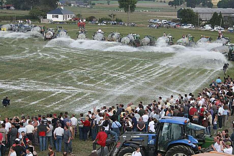 French farmers spray milk onto a field in Ardevon near Le Mont Saint-Michel, western France, to protest falling milk prices, Friday, Sept. 18, 2009. Farmers around Europe are dumping milk in protests to call attention to falling milk prices and a plan to phase out milk quotas. The EU Farm Commissioner responded Thursday Sept. 17, 2009 by offering extra help to dairy farmers. Farmers using 300 tractors in Ardevon sprayed 3,5 million liters (921 683 gallons) of fresh milk onto fields on Friday. (AP Photo/David Vincent) Photo: David Vincent, AP