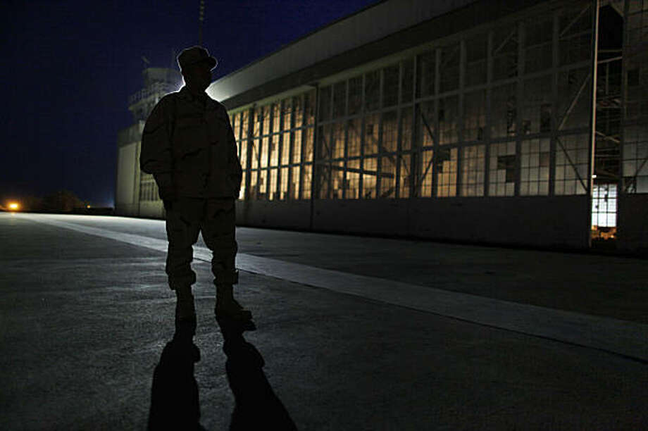 This photo, reviewed by the US military, shows a US military trooper standing in front of an old airplane hangar used for media activities, before dawn, at Camp Justice, site of the US war crimes tribunal compound at Guantanamo Bay US Naval Base, Cuba, July 15, 2009. Hearings in four separate cases are being held July 15th & 16th, including the case titled US vs Mohammed, with Khalid Sheikh Mohammed and four fellow September 11, 2001 attack defendants.  AFP PHOTO / Pool / Brennan Linsley (Photo credit should read BRENNAN LINSLEY/AFP/Getty Images) Photo: Brennan Linsley, AFP/Getty Images