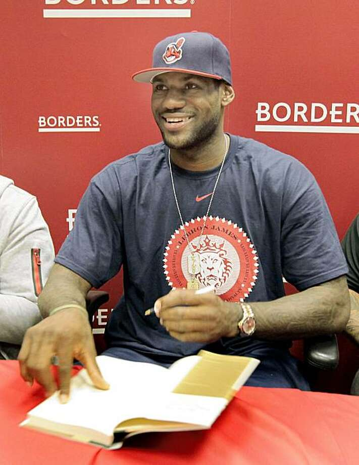 """NBA star and Cleveland Cavalier LeBron James smiles at a fan as he signs a copy of his new book """"Shooting Stars"""" at a Borders bookstore in Westlake, Ohio on Friday, Sept. 18, 2009.  In the book, co-authored with Buzz Bissinger, James tells the story of his rise from Akron, Ohio, hoops prodigy to NBA superstar. (AP Photo/Amy Sancetta) Photo: Amy Sancetta, AP"""