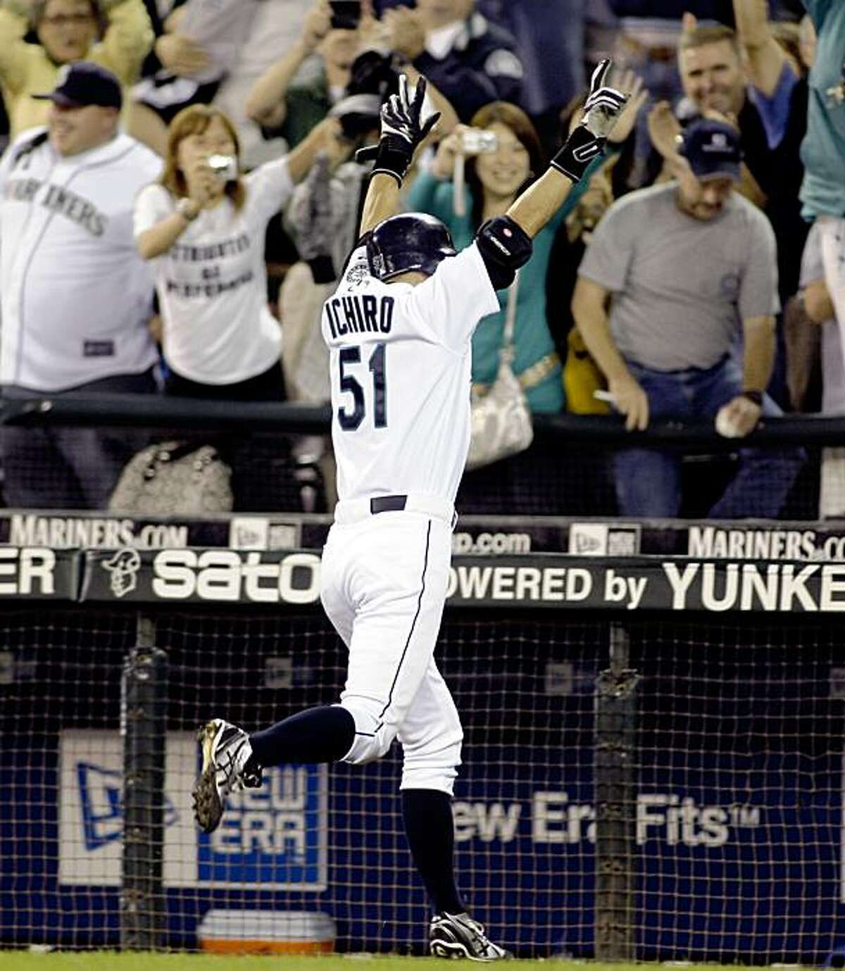 Seattle Mariners' Ichiro Suzuki (51) celebrates with fans after he hit a walk-off RBI-single in the 14th inning that gave the Mariners a 4-3 win over the Chicago White Sox, Thursday, Sept. 17, 2009, in an extra-innings baseball game at Safeco Field in Seattle. (AP Photo/Ted S. Warren)