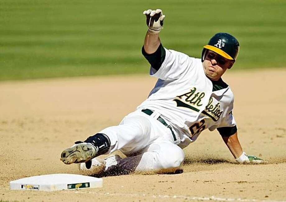 Oakland Athletics' Cliff Pennington slides safely into third base as he drives in two runs with a triple against the Texas Rangers during the seventh inning of a baseball game in Oakland, Calif., Thursday, Sept. 24, 2009. (AP Photo/Marcio Jose Sanchez) Photo: Marcio Jose Sanchez, AP