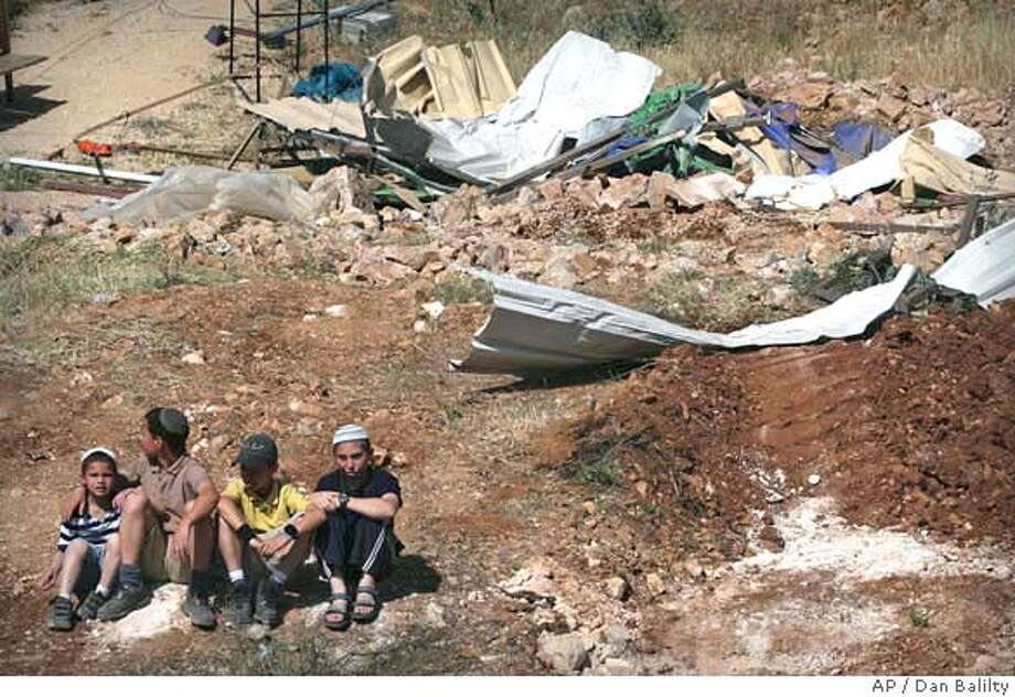 Israeli settlers sit at a site where Israeli police demolished a building on the border of the Jewish settlement of Kiryat Arba and the West Bank city of Hebron Sunday, May 4, 2008. The Israeli police evacuated the area calling it an illegal outpost. (AP Photo/Dan Balilty) Photo: DAN BALILTY
