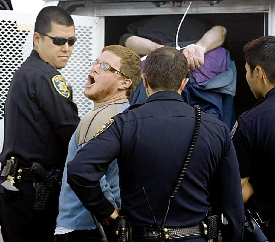 An unidentified protester shouts at supporters as he's led to a police van after he was arrested for disrupting a meeting of the Board of Regents at the UCSF Mission Bay campus to demonstrate against proposed fee hikes in San Franciscoo on Wednesday. More than a dozen protesters were arrested. Photo: Paul Chinn, The Chronicle