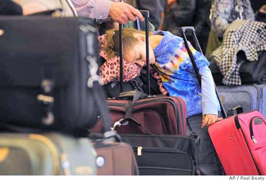 ** FILE ** In this Wednesday, April 9, 2008 file photo, Trinity Maughan, 6, of Peoria Ill. rests on a bag while waiting in line at O'Hare International Airport in Chicago. For travelers, a vacation season of jammed planes, delayed flights and higher fares looms in what's shaping up as the worst of times for both airlines and their customers. (AP Photo/Paul Beaty, file) Photo: Paul Beaty