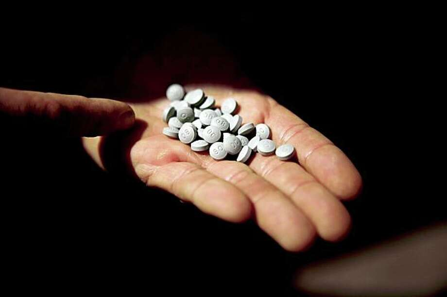 Sergeant Mark Obrochta, of the Tenderloin Plain Clothes Street Crimes Unit, displays a handful of OxyContin pills recovered from a drug bust suspect in the Tenderloin district in San Francisco, Calif. on Tuesday, Sept. 15, 2009. As part of new police chief George Gascon's Tenderloin sweeps, officers in the district are targeting drug deals within the radius of schools for a drug-free school zone per California Health And Safety Code 11353.6 where violators will then be persecuted with extra prison terms. Photo: Stephen Lam, The Chronicle