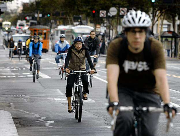Bicycle commuters have room to ride on eastbound Market Street after traffic was forced to turn right at Eighth Street in San Francisco on Tuesday. Taxis, buses, commercial vehicles and bicyclists are exempt in the six-week pilot program, which started today, and is designed to ease congestion on Market Street through the dense downtown core. Photo: Paul Chinn, The Chronicle