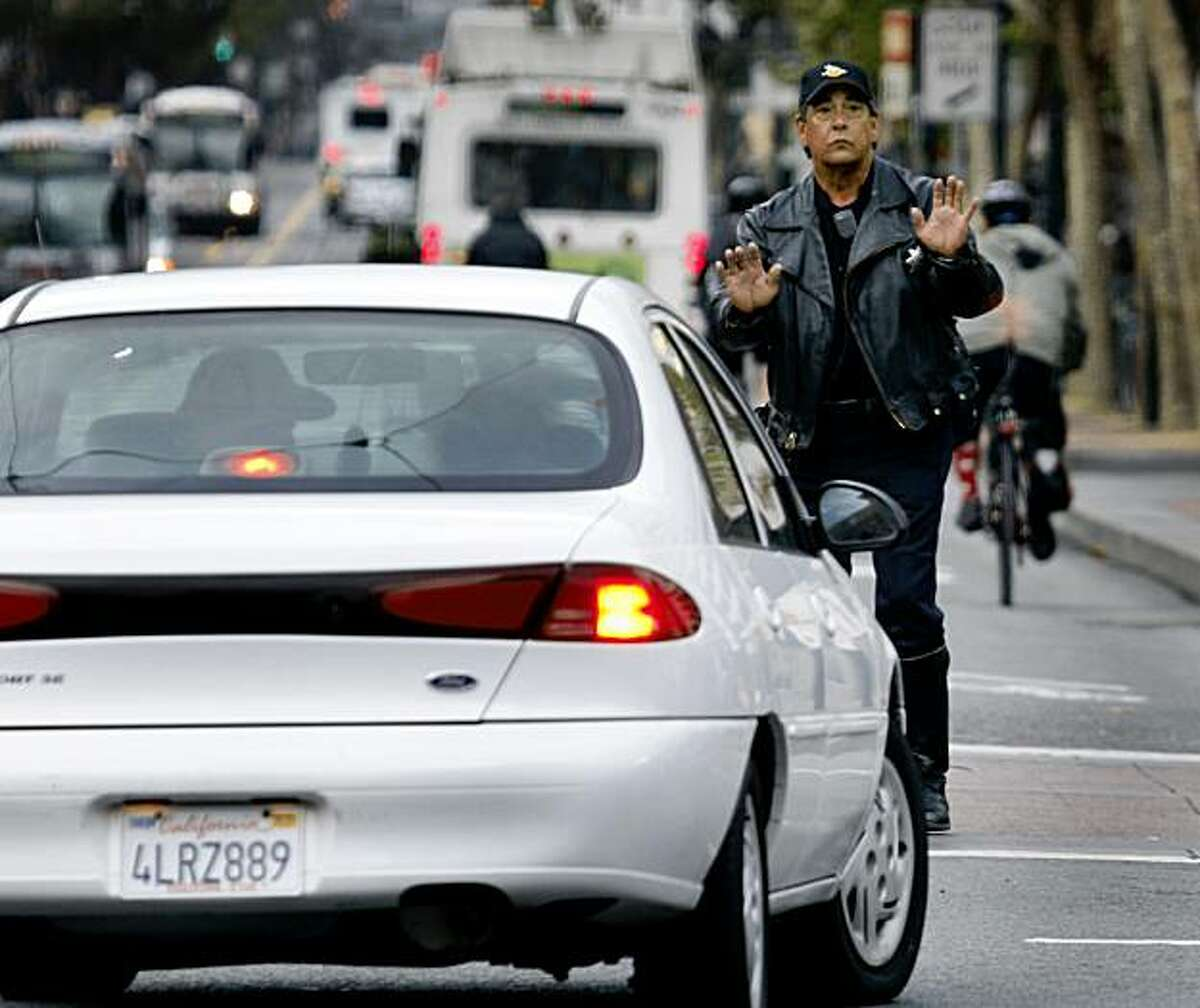 Police officer Dave Kranci stops a motorist from travelling eastbound on Market Street and forces them to turn right at Eighth Street in San Francisco Tuesday morning.