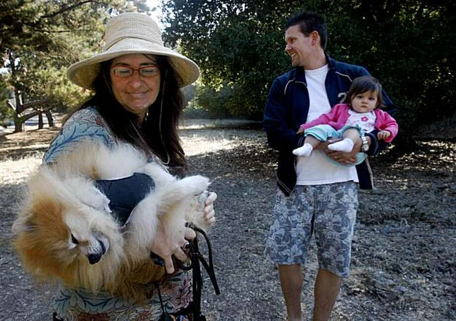 Morrisa Sherman (left) cradles her pomeranian Fizgig and Will Wood holds his daughter Desiree during a visit to Blair Park on Moraga Avenue in Piedmont, Calif., on Friday, Sept. 25, 2009. A group of residents are fighting plans for a sports complex on the narrow strip of land citing safety and traffic concerns. Photo: Paul Chinn, The Chronicle