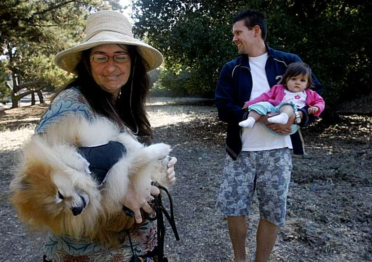 Morrisa Sherman (left) cradles her pomeranian Fizgig and Will Wood holds his daughter Desiree during a visit to Blair Park on Moraga Avenue in Piedmont, Calif., on Friday, Sept. 25, 2009. A group of residents are fighting plans for a sports complex on the narrow strip of land citing safety and traffic concerns.