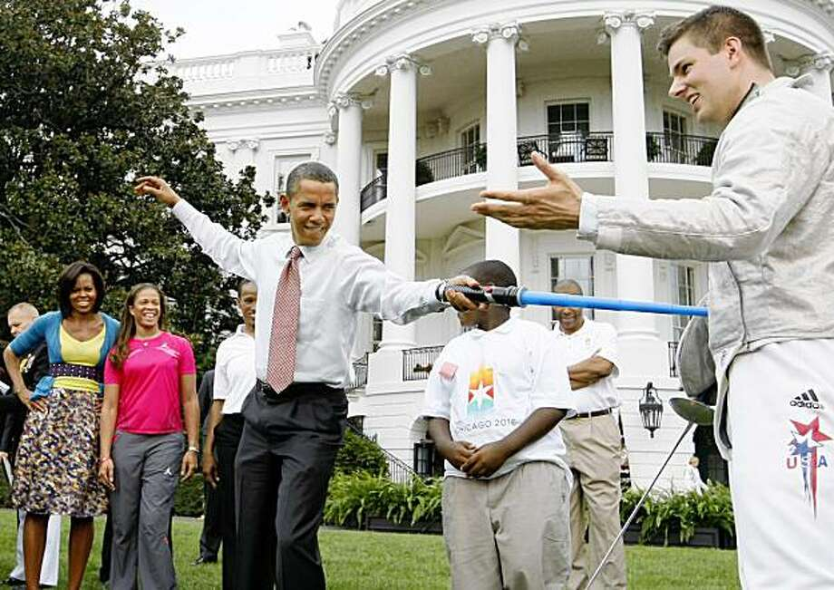 """FILE - In this Sept. 16, 2009 file photo, President Barack Obama uses a light saber as he """"attacks"""" Olympic fencer Tim Morehouse who won a silver medal in Men's Saber Fencing at the Beijing Olympics. Obama will travel to Denmark to support Chicago's bid for the 2016 Summer Olympics, projecting the highest-ever White House profile in lobbying for the international event. (AP Photo/Charles Dharapak) Photo: Charles Dharapak, AP"""