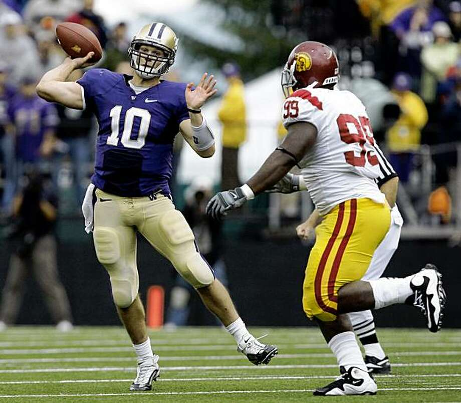 Washington quarterback Jake Locker (10) passes as Southern California's Averell Spicer moves in during the second half of an NCAA college football game Saturday, Sept. 19, 2009, in Seattle. Locker connected with Jermaine Kearse on the play for 19 yards and a first down on the final drive of the game. Washington upset USC 16-13. (AP Photo/Elaine Thompson) Photo: Elaine Thompson, AP