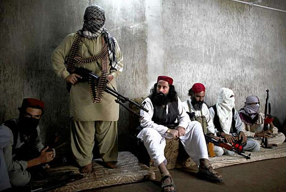 In this photo taken on Monday, Sept. 7, 2009, Taliban commander Baz Mohammed, center, speaks during an interview with the Associated Press at his headquarters in Dera Ismail Khan, Pakistan. Mohammed, a commander in a pro-government militia, is supported by the government as both share a common enemy, the Pakistan Taliban serving under the replacement of their chief Baitullah Mehshud, killed during a CIA missile strike last month. (AP Photo/Alexandre Meneghini) Photo: Alexandre Meneghini, AP