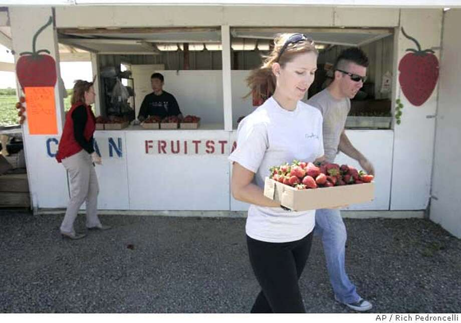 ###Live Caption:Sarah Feilmoser second from right, accompanied by Steve Van Horn,, right, carries a box of strawberry's purchased from Chan's strawberry stand, picks strawberry's in a field next to his stand in Brentwood, Calif., Tuesday, April 15, 2008. A bill in the Assembly by David Jones, D-Sacramento, would ease restrictions that make it costly for farmers to sell more than fresh fruit at their road side stands. Current law requires farm stands to meet a variety of regulations designed for grocery stores.(AP Photo/Rich Pedroncelli)###Caption History:Sarah Feilmoser second from right, accompanied by Steve Van Horn,, right, carries a box of strawberry's purchased from Chan's strawberry stand, picks strawberry's in a field next to his stand in Brentwood, Calif., Tuesday, April 15, 2008. A bill in the Assembly by David Jones, D-Sacramento, would ease restrictions that make it costly for farmers to sell more than fresh fruit at their road side stands. Current law requires farm stands to meet a variety of regulations designed for grocery stores.(AP Photo/Rich Pedroncelli)###Notes:###Special Instructions: Photo: Rich Pedroncelli