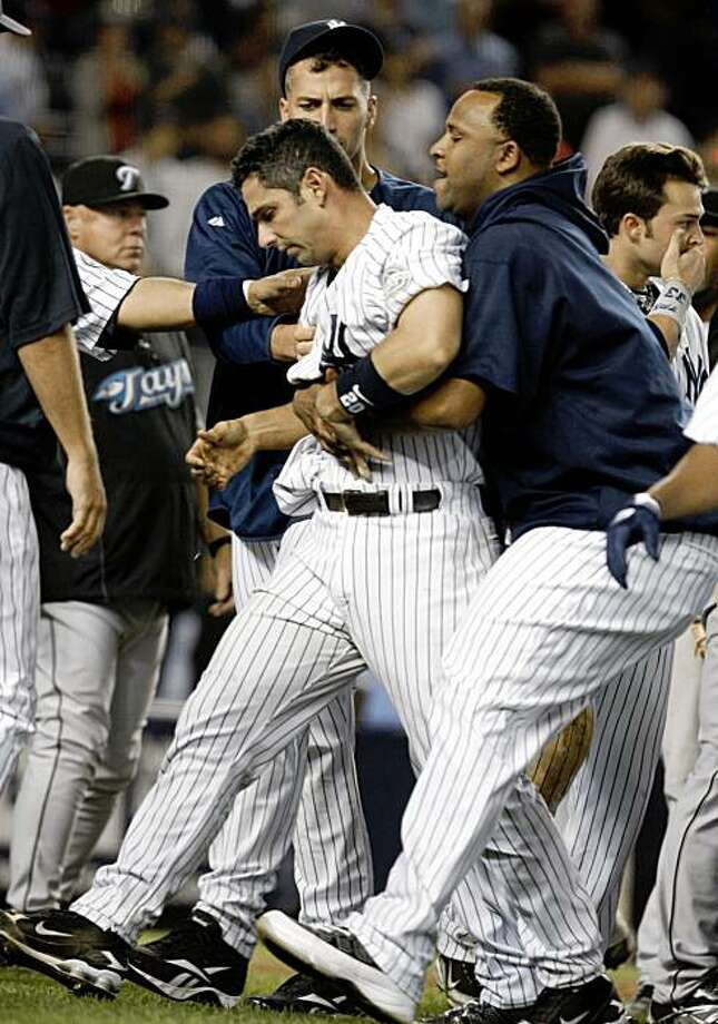New York yankees pitchers Andy Pettitte, rear, and CC Sabathia, right, escort teammate Jorge Posada from the field after Posada was involved in an eighth-inning fight with Toronto Blue Jays pitcher Jesse Carlson in a baseball game at Yankee Stadium on Tuesday, Sept. 15, 2009, in New York. (AP Photo/Kathy Willens) Photo: Kathy Willens, AP