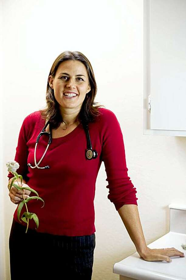 Holding a strand of eupatorium perfoliatum plant, Dr. Karen Peters, a licensed Doctor of Naturopathic Medicine, stands for a portrait at her office in Albany, Calif. on Tuesday, Sept. 8, 2009. The plant, commonly known as boneset, is used by naturopathic doctors to treat influenza, deep muscle and bone aches, as well as to stimulate innate immunity. It was used successfully against the 1918 influenza epidemic, according to Dr. Peters. Photo: Stephen Lam, The Chronicle