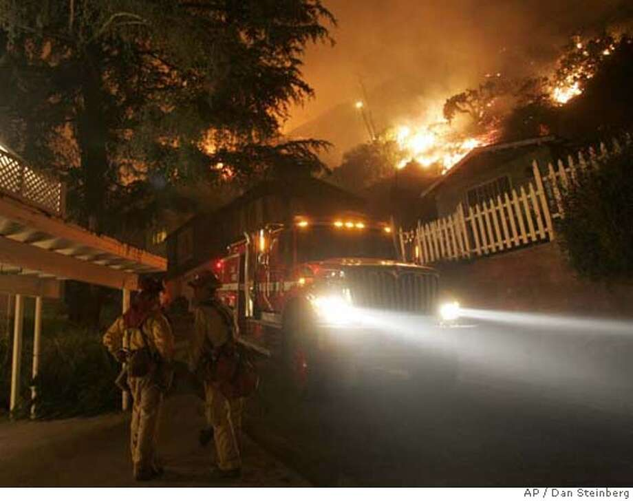 ###Live Caption:Firefighters confer as they protect homes from a wind driven brush fire in the foothills of Sierra Madre, Calif. on Monday, April 28, 2008. A flare up early Monday morning caused the fire to push towards and threaten numerous homes in the town of Sierra Madre. (AP Photo/Dan Steinberg)###Caption History:Firefighters confer as they protect homes from a wind driven brush fire in the foothills of Sierra Madre, Calif. on Monday, April 28, 2008. A flare up early Monday morning caused the fire to push towards and threaten numerous homes in the town of Sierra Madre. (AP Photo/Dan Steinberg)###Notes:###Special Instructions: Photo: Dan Steinberg