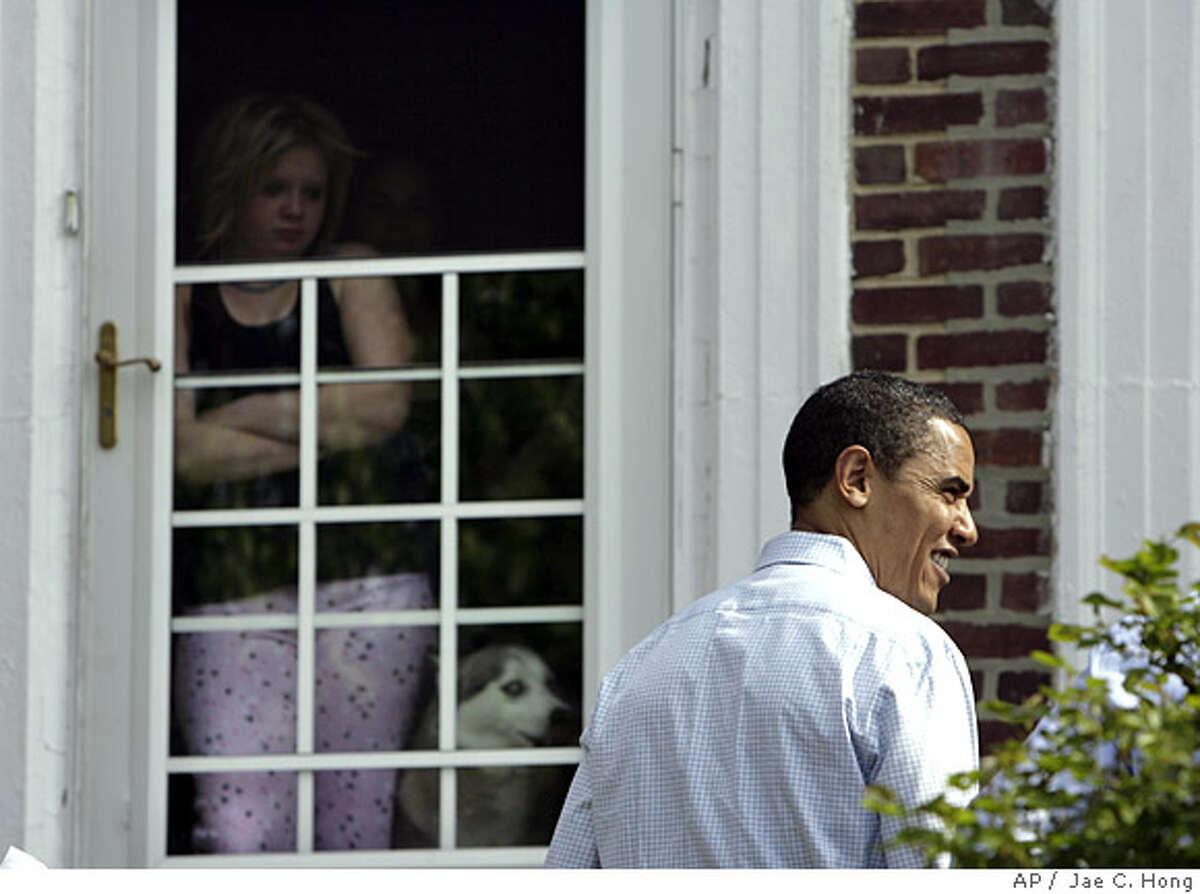 A woman watches as Democratic presidential hopeful, Sen. Barack Obama, D-Ill., right, campaigns door to door in Philadelphia, Saturday, April 19, 2008. (AP Photo/Jae C. Hong)