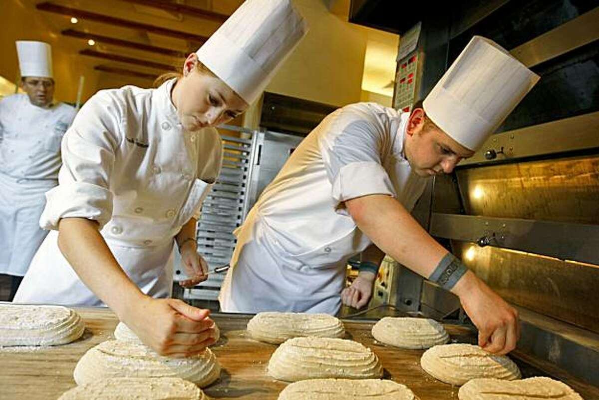 One of the four Baking and Pastry Instructors Aaron Brown (left) watches over Sarah Hammord and Joshua Wharton as they cut the loaves of bread before baking, in the Hearth Bread and Roll class, at the Culinary Institute, Wednesday August 2, 2009, in St. Helena, Calif.