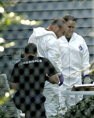 Police work in the back yard of a home where four people were murdered in Farmville, Va., Monday, Sept. 21, 2009. Prosecutors said Monday they had to investigate hundreds of pieces of forensic evidence in their case against an aspiring 20-year-old rapper from California suspected of killing a Virginia pastor and three other people. Richard Alden Samuel McCroskey III made his first court appearance by video in Prince Edward County and was appointed attorney Cary Bowen, who was not present and said he had not talked to the suspect. A preliminary hearing was set for Jan. 11 because of the amount of evidence discovered.  (AP Photo/Richmond Times-Dispatch, P. Kevin Morley) Photo: P. Kevin Morley, AP