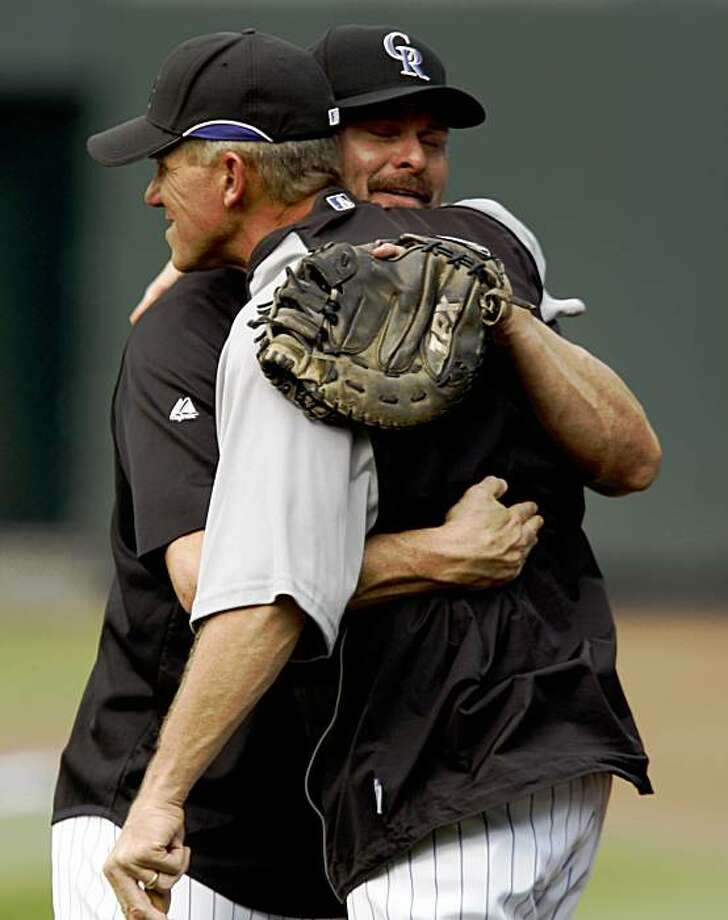 Colorado Rockies manager Jim Tracy, front, hugs Jason Giambi after he took part in his first batting practice since being recalled from the team's Triple A affiliate in Colorado Springs as the Rockies prepare to face the New York Mets in a baseball game in Denver on Tuesday, Sept. 1, 2009. (AP Photo/David Zalubowski) Photo: David Zalubowski, AP