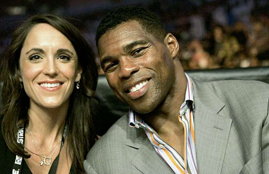 FILE - In this Aug. 15, 2009 file photo, former NFL running back Herschel Walker, right, and Amanda Lyne are seen at a Strikeforce mixed martial arts event in San Jose, Calif. Walker is starting a new career in mixed martial arts, saying Monday, Sept. 21, 2009, that he has signed a multi-fight contract with promoter Strikeforce. Walker will begin a 12-week training camp next month in San Jose. The 1982 Heisman Trophy winner already holds a fifth-degree black belt in Tae Kwon Do.  (AP Photo/Jeff Chiu, File) Photo: Jeff Chiu, AP